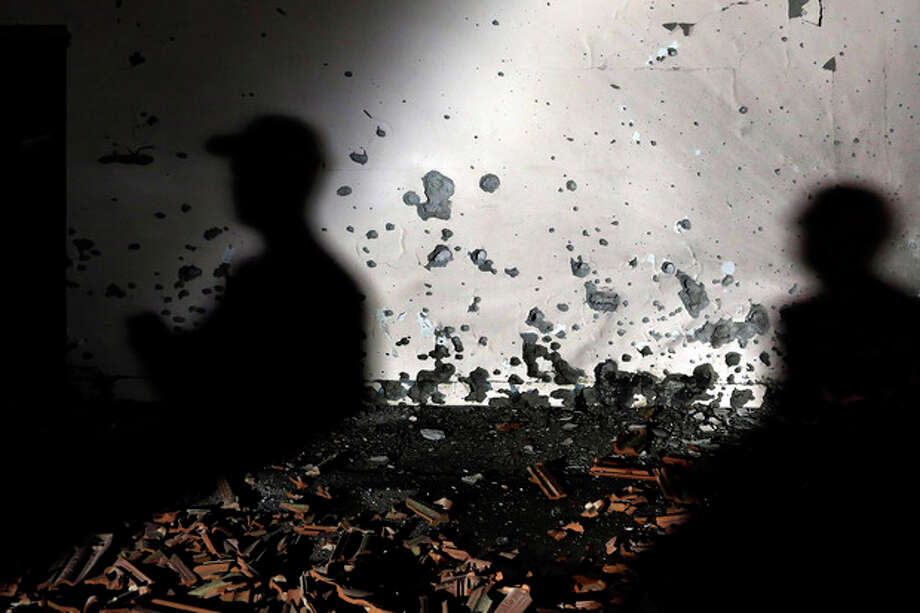 Israeli soldiers examine a damaged wall of a house hit by a rocked fired from the Gaza Strip at Be'er Tuvia Regional Council, Friday, Nov. 16, 2012. Fierce clashes between Israeli forces and Gaza militants are continuing for the third day. (AP Photo / Tsafrir Abayov) / AP