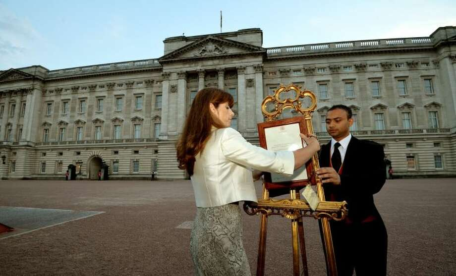 The Queen's Press Secretary Ailsa Anderson with Badar Azim, a footman, places an official document to announce the birth of a baby boy, at 4.24pm to the William and Kate, the Duke and Duchess of Cambridge at St Mary's Hospital, in the forecourt of Buckingham Palace in London Monday July 22, 2013. The child is now third in line to the British throne. (AP Photo/John Stillwell, Pool)