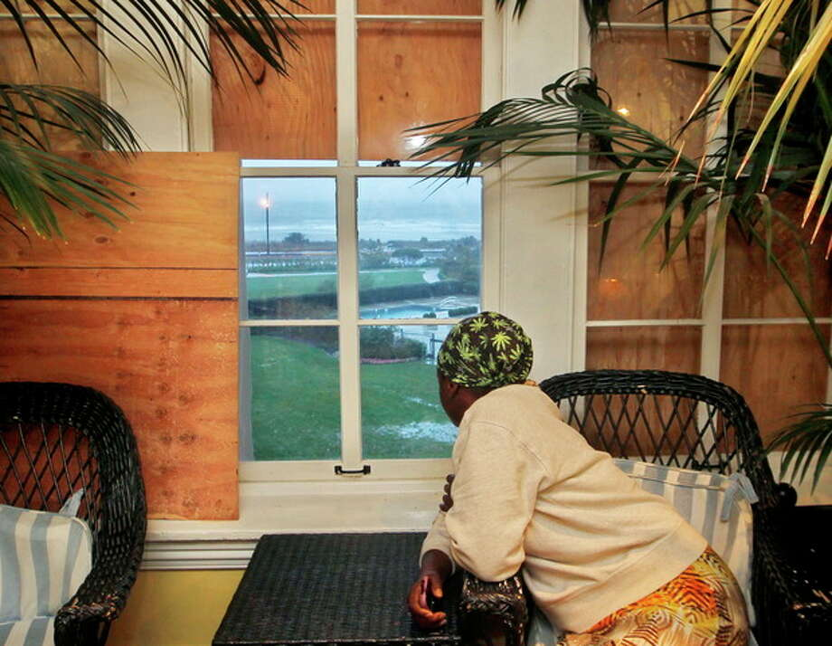 FILE - This Oct. 29, 2012 file photo shows Judiann Parker looking out through a partially boarded-up window at the Atlantic Ocean before the arrival of superstorm Sandy in Cape May, N.J. Despite days of dire forecasts and explicit warnings, hundreds of thousands of people in New York and New Jersey ignored mandatory evacuation orders as Superstorm Sandy closed in. Now, after scores of deaths and harrowing escapes, emergency officials say they will look at what more can be done to persuade residents to get out when their lives are in danger. (AP Photo/Mel Evans, File) / AP