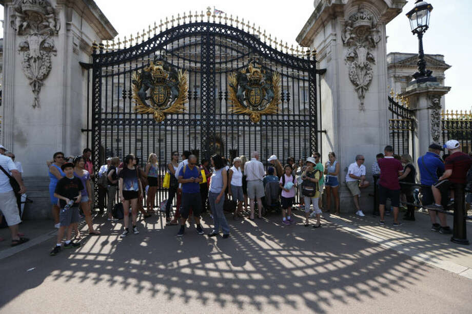 People look at Buckingham Palace in London where a notice announcing the birth of the baby will be posted, Monday, July 22, 2013. Buckingham Palace officials say Prince William's wife, Kate, Duchess of Cambridge, has been admitted to St Mary's Hospital in the early stages of labour. (AP Photo/Sang Tan)