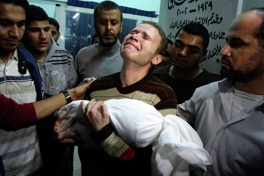 Jihad Masharawi weeps while he holds the body of his 11-month old son Ahmad, at Shifa hospital following an Israeli air strike on their family house, in Gaza City, Wednesday, Nov. 14, 2012. The Israeli military said its assassination of the Hamas military commander Ahmed Jabari, marks the beginning of an operation against Gaza militants. (AP Photo/Majed Hamdan) / AP