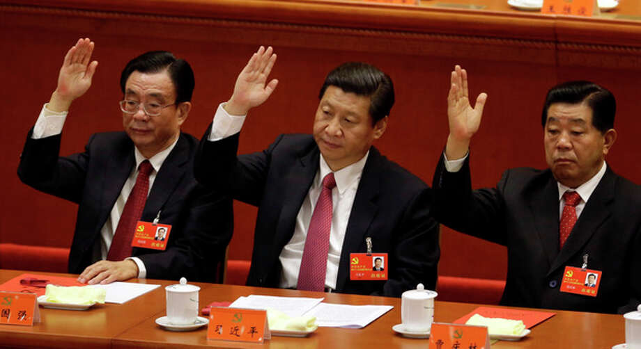 Chinese vice President Xi Jinping, center, Central Commission for Discipline Inspection head He Guoqiang, left, and Chinese People's Political Consultative Conference Chairman Jia Qinglin raise their hands to show approval for a work report during the closing ceremony for the 18th Communist Party Congress held at the Great Hall of the People in Beijing, China, Wednesday Nov. 14, 2012. (AP Photo/Lee Jin-man) / AP