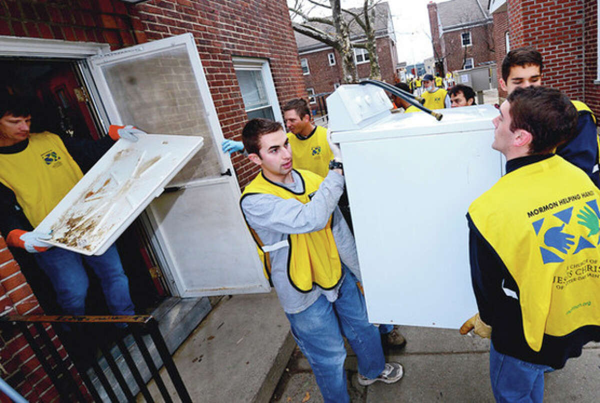 Nearly 200 members of the Church of Latter Day Saints Helping Hands crew clean up units at Washington Village Saturday. Hour photo / Erik Trautmann