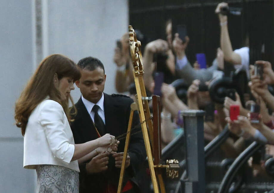 Members of the public lean in to take pictures as the Queen's Press Secretary Ailsa Anderson with Badar Azim, a footman, put up a notice proclaiming the birth of a baby boy to Prince William and Kate, Duchess of Cambridge on display for public view at Buckingham Palace in London, Monday, July 22, 2013. (AP Photo/Sang Tan)