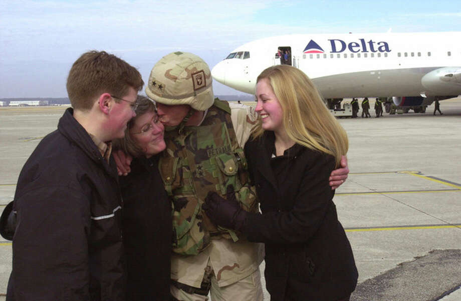 FILE - In this Feb. 14, 2004 file photo, Maj. Gen. David Petraeus, center, commanding general of the 101st Airborne Division, kisses his wife, Holly, second left, as his son, Stephen, left, and daughter, Anne, right, look on upon his return home from Iraq to Fort Campbell, Ky. Gen. Petraeus, the retired four-star general who led the U.S. military campaigns in Iraq and Afghanistan, resigned Friday, Nov. 9, 2012 as director of the CIA after admitting he had an extramarital affair. (AP Photo/Christopher Berkey, File) / FR34473 AP