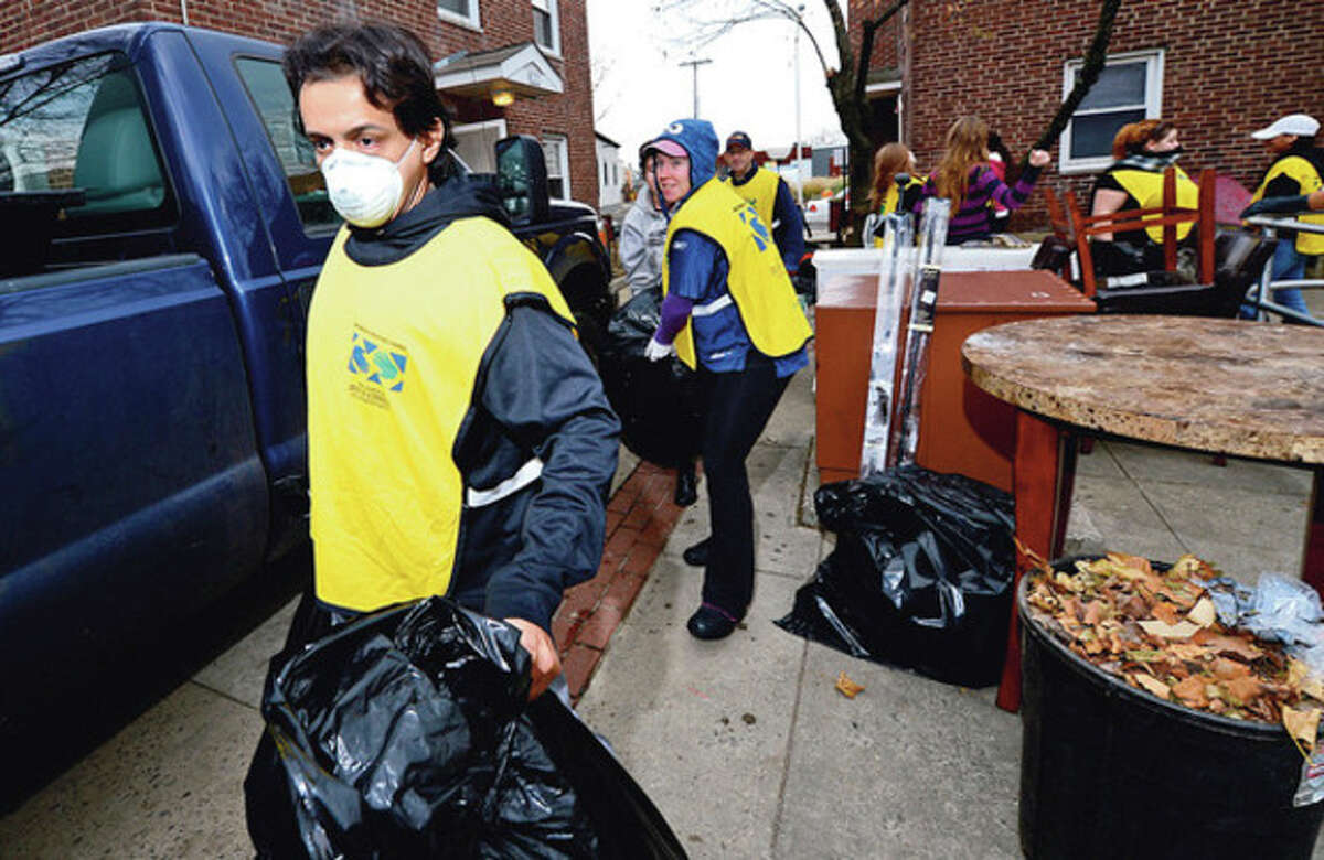 Nearly 200 members of the Church of Latter Day Saints Helping Hands crew including Joshua Chaboyu clean up units at Washington Village Saturday. Hour photo / Erik Trautmann