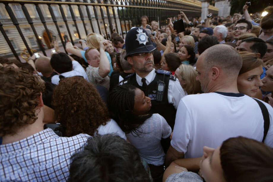 A police officer, center, tries to control a crowd of people trying to get to the railing to take pictures of a notice proclaiming the birth of a baby boy to Prince William and Kate, Duchess of Cambridge on display for public view at Buckingham Palace in London, Monday, July 22, 2013. (AP Photo/Sang Tan)