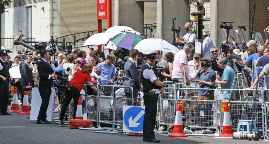 A British police officer, backdropped by members of the media, stands outside St. Mary's Hospital exclusive Lindo Wing in London, Monday, July 22, 2013. Buckingham Palace officials say Prince William's wife, Kate, has been admitted to the hospital in the early stages of labour. Royal officials said that Kate traveled by car to St. Mary's Hospital in central London. Kate _ also known as the Duchess of Cambridge _ is expected to give birth in the private Lindo Wing of the hospital, where Princess Diana gave birth to William and his younger brother, Prince Harry.The baby will be third in line for the British throne _ behind Prince Charles and William _ and is anticipated eventually to become king or queen.(AP Photo/Lefteris Pitarakis)