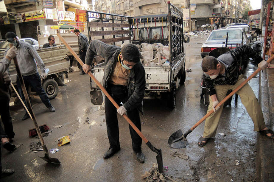 In this Saturday, Nov. 10, 2012 photo, activists collect garbage from the streets of Aleppo, Syria. Three months after Free Syrian Army fighters brought the war to Aleppo, street cleaning and garbage pickup services collapsed because of fighting and shelling. (AP Photo/Mónica G. Prieto) / AP