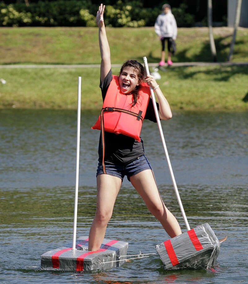 "Claudia Fernandez celebrates as she crosses the finish line during a ""Walk on Water"" event at Florida International University in Miami, Thursday, Nov. 8, 2012. Students at FIU walked on water wearing water shoes they built as part of a class assignment on Thursday. Students must make it to the other side of a 175-foot lake on campus while wearing the aquatic shoes in order to get an ""A'' on the assignment, and the first student to do so wins $500. (AP Photo/Alan Diaz) / AP"