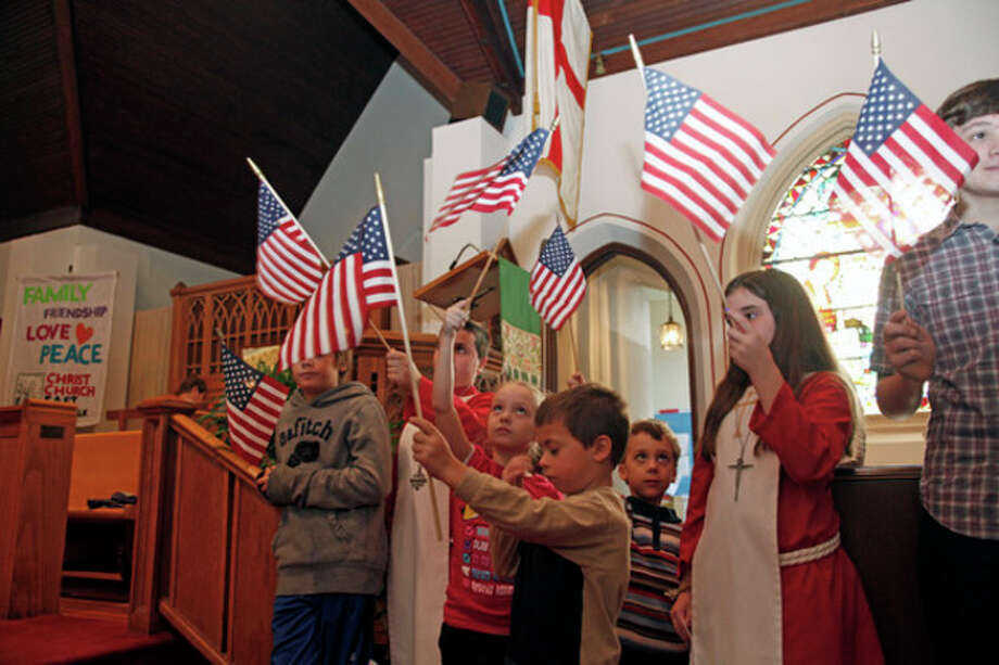 Children wave American flags during Christ Episcopal Church's service honoring veterans of the armed forces Sunday morning in Norwalk.Hour Photo / Danielle Robinson
