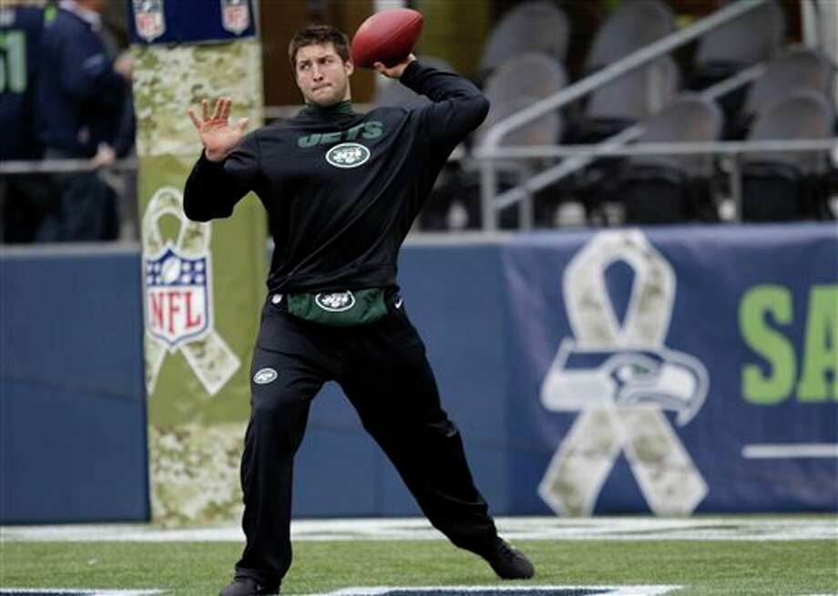 "New York Jets backup quarterback Tim Tebow warms up next to camouflage logos for the NFL's ""Salute to Service"" tribute to military veterans, prior to an NFL football game against the Seattle Seahawks, Sunday, Nov. 11, 2012, in Seattle. (AP Photo/Ted S. Warren) / AP"
