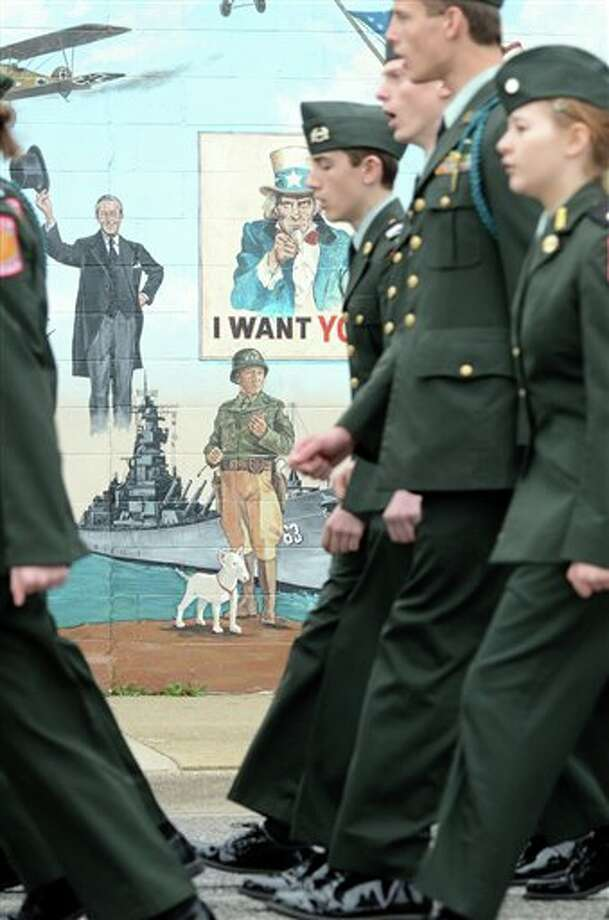 A vintage Uncle Sam recruiting poster beckons from the side of Terre Haute Indiana's new Veteran's Memorial Museum as the Terre Haute South Vigo High School Army Junior ROTC marches past in the Veteran's Day parade Sunday Nov. 11, 2012. (AP Photo/Tribune-Star, Jim Avelis) / Tribune-Star