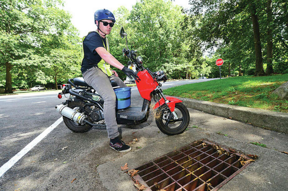 Ethan Falla of All Habitat puts larvacide in to public storm drains throughout the city of Norwalk Wednesday.Hour photo / Erik Trautmann / ©2012 Pascal Photographic Studios