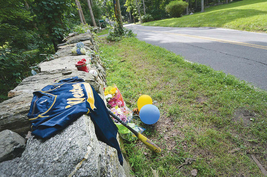 A baseball jersey and bat along with items like a stuffed tiger and flowers lay on a stone wall along Cedar Road in memory of Joseph 'A.J.' Cina.