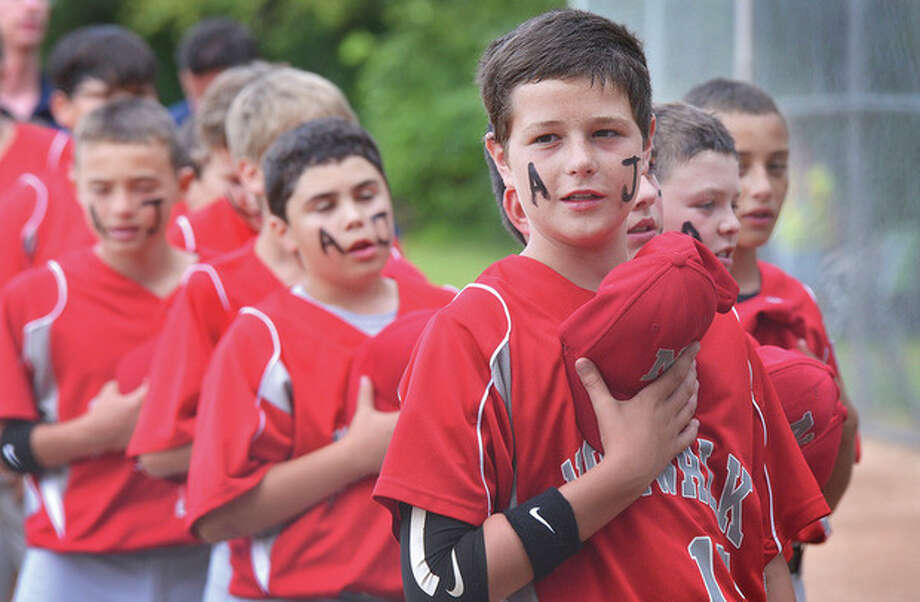 Hour Photo/Alex von KleydorffMembers of the Norwalk Little League team observe a moment of silence for AJ Cina, the 12-year-old Weston Little Leaguer who died in a bicycle accident this week.