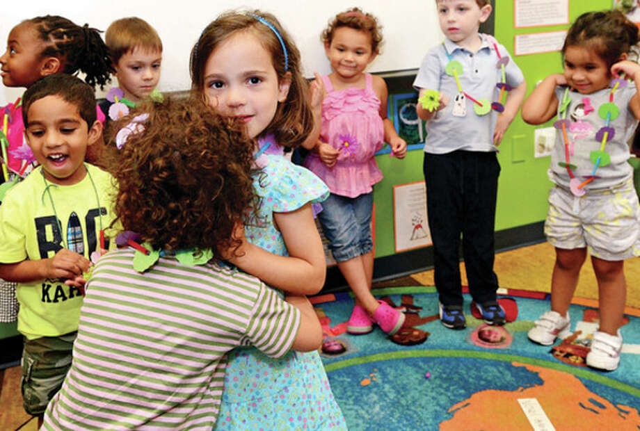 Lone graduate Brianna Pullia receives congratulations from fellow students during the Early Language and Literacy Initiative (ELLI) at Stepping Stones graduation ceremony Wednesday. The Intiative is a collaboration of four prominent local organizations and the lab school is the cornerstone of the partnership.Hour photo / Erik Trautmann / (C)2013, The Hour Newspapers, all rights reserved