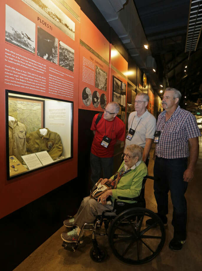 Mary Jerstad Jacobs, sister of Maj. John Jerstad, who was awarded a Medal of Honor on the Ploesti Raid in World War II, views a display on the raid while touring the United States Air Force Museum with her sons, left to right, Scott Jacobs, Jeff Jacobs, and Peter Jacobs, Wednesday, July 31, 2013, in Dayton, Ohio. The planes flew a dangerous low altitude raid on Aug. 1, 1943, targeting heavily defended oil fields in occupied Romania. Survivors of the raid are having a 70th reunion Thursday in Dayton. (AP Photo/Al Behrman)