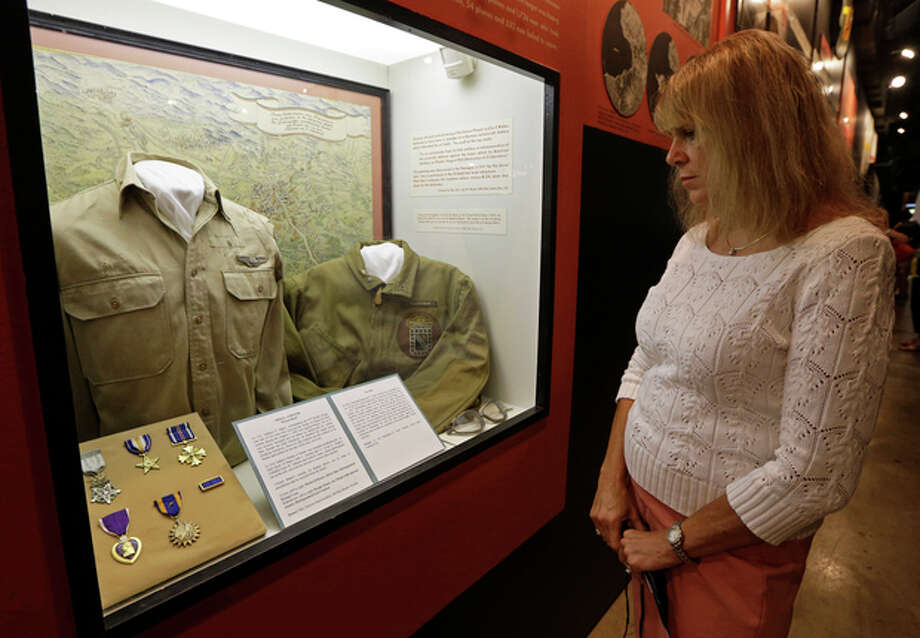 Karen Warner views a display on the Ploesti Raid in World War II that shows a shirt worn by her father, Lt. Col. Jack Warner, while touring the United States Air Force Museum, Wednesday, July 31, 2013, in Dayton, Ohio. The planes flew a dangerous low altitude raid on Aug. 1, 1943, targeting heavily defended oil fields in occupied Romania. Survivors of the raid are having a 70th reunion Thursday in Dayton. (AP Photo/Al Behrman) / AP