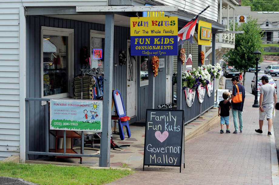 A family leaves the Family Fun Kuts business in the Sandy Hook section of Newtown, Conn., Wednesday, July 31, 2013. Gov. Dannel P Malloy visited Wednesday to meet with business owners and talk about economic recovery after the December elementary school shooting that killed 20 students and six adults. (AP Photo/Jessica Hill) / FR125654 AP