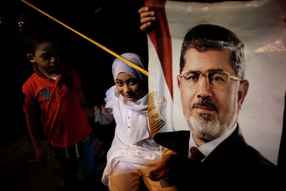 "An Egyptian child stands next to poster of the Egypt's ousted President Mohammed Morsi outside Rabaah al-Adawiya mosque, where supporters have installed a camp and hold daily rallies at Nasr City, in Cairo, Egypt, Wednesday, July 31, 2013. Egypt's military-backed government has ordered the police to break up the sit-in protests by supporters of ousted President Mohammed Morsi, saying they pose an ""unacceptable threat"" to national security. Information Minister Dorreya Sharaf el-Din said in a televised statement Wednesday that the police are to end the demonstrations ""within the law and the constitution."" (AP Photo/Hassan Ammar) / AP"