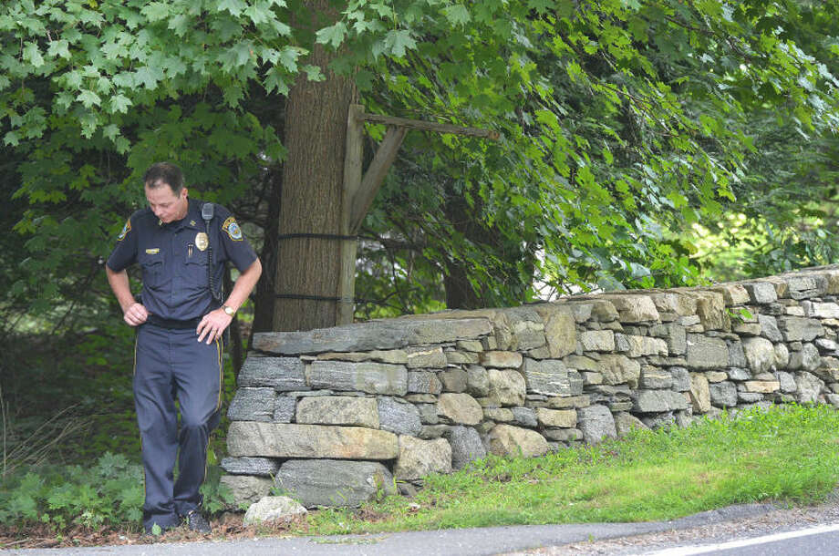 Hour Photo/Alex von Kleydorff . On Tuesday, Wilton Police investigate an area along Cedar rd in Wilton, the site of a fatal bicycle accident on Monday evening. Captain john Lynch checks along a stone wall next to the road.