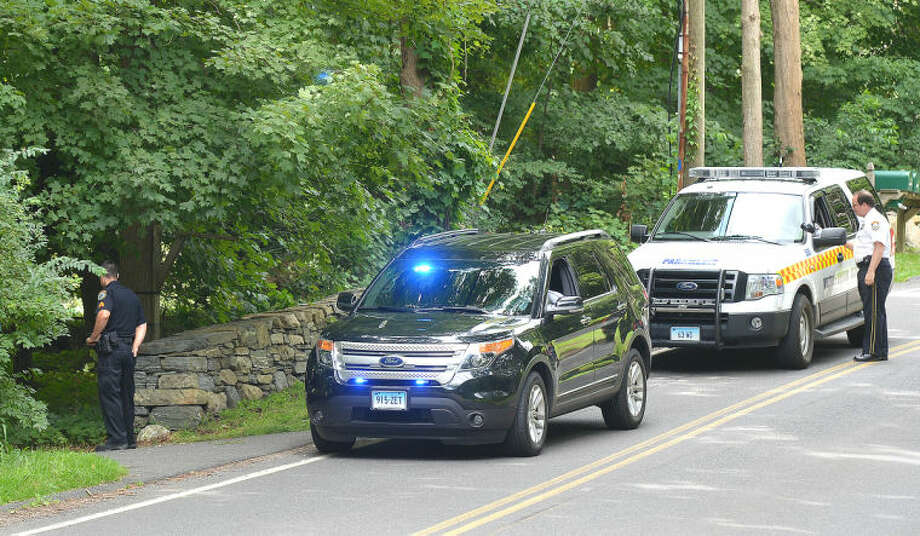 Hour Photo/Alex von Kleydorff . On Tuesday, Wilton Police investigate an area along Cedar rd in Wilton, the site of a fatal bicycle accident on Monday evening.