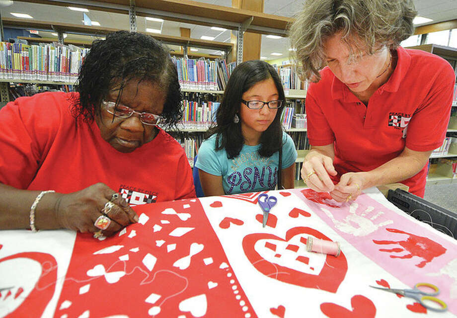 Hour Photo/Alex von KleydorffLizzy Rocwell gets 11-year-old Natalie Roman started on her section of quilt as Viola Sears works on her section, during a quilting Bee at Norwalk public Library.