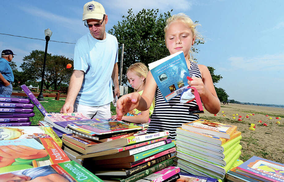Scott Schweiter and his daughters Jessica, 9, and Ella, 6, look for books during a beach party at Calf Pasture Beach for children enrolled inNorwalk ACTS(Achievement, Community, Teams and Success) summer reading program, DigInto Reading, Saturday. Hour photo / Erik Trautmann / (C)2013, The Hour Newspapers, all rights reserved
