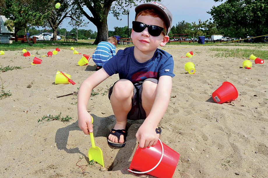 Holden Legette, 5, digs for buried treasure during a beach party at Calf Pasture Beach for children enrolled in Norwalk ACTS summer reading program, Dig Into Reading, Saturday. Hour photo / Erik Trautmann / (C)2013, The Hour Newspapers, all rights reserved