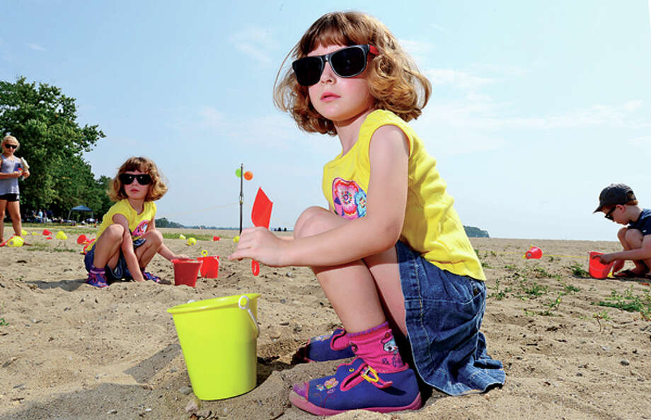 Victoria and Alexandra Jankowski, both 4, dig for buried treasure during a beach party at Calf Pasture Beach for children enrolled inNorwalk ACTSsummer reading program, DigInto Reading, Saturday. Hour photo / Erik Trautmann / (C)2013, The Hour Newspapers, all rights reserved
