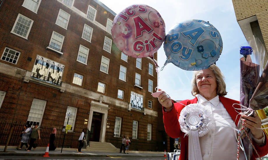 FILE - In this Monday, July 15, 2013 file photo royal supporter Margaret Tyler displays balloons for the media in front of the Lindo Wing at St Mary's Hospital in London. By the time you're reading this, the Duchess of Cambridge could be in labor. Or it could be a matter of hours. Or days. Or weeks. As Britain's Prince William and his wife, Kate, await the birth of their first child _ and the next heir to the English throne _ some are convinced the royal due date has already passed, even though the Palace has not given an exact date. Many in the British media predicted the baby would be born last week and the Prince himself is now on official leave. (AP Photo/Kirsty Wigglesworth, File) / AP