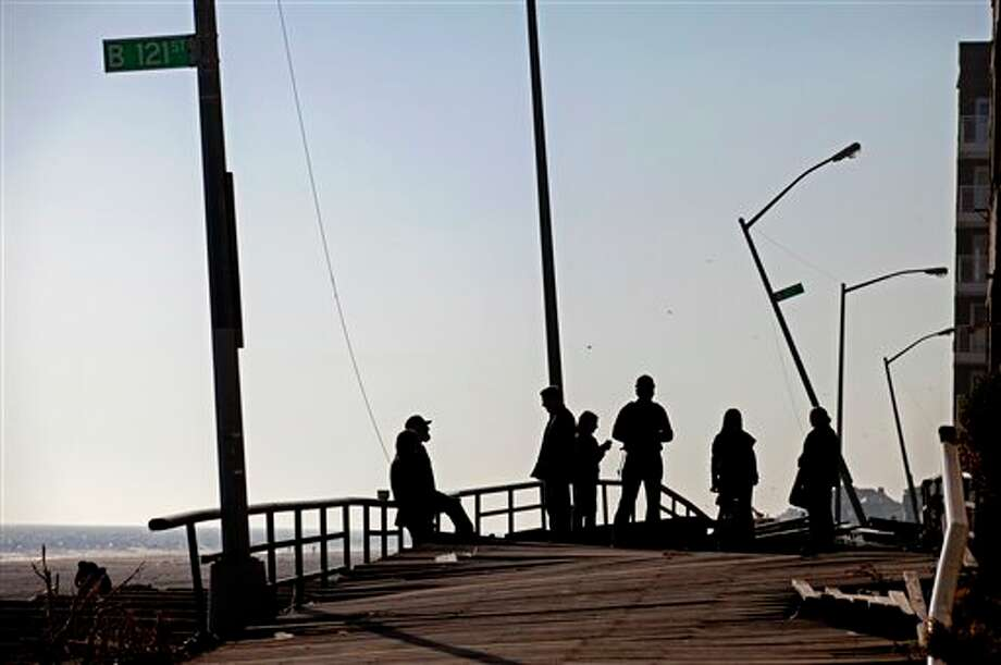 People gather on the buckled boardwalk of the Rockaway Park neighborhood of the borough of Queens, New York, Sunday, Nov. 11, 2012, in the wake of Superstorm Sandy. (AP Photo/Craig Ruttle) / FR61802 AP