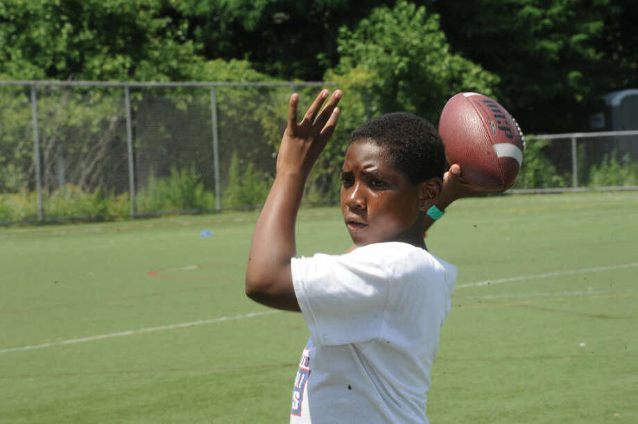 Koran McKelvy throws a spiral during the youth football camp at Stamford High School, where former New York Giants star Curtis McGriff spoke to participants in the camp.
