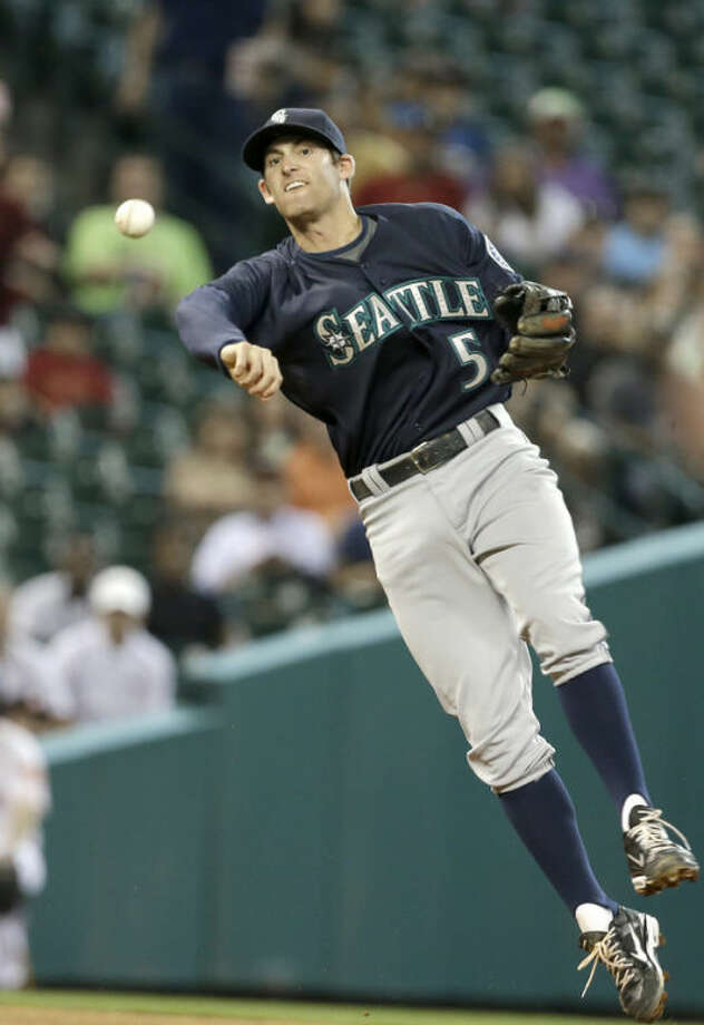 Seattle Mariners shortstop Brad Miller throws to first base too late for the out, on an RBI single by Houston Astros' Jason Castro in the fifth inning of a baseball game Saturday, July 20, 2013, in Houston. (AP Photo/Pat Sullivan)