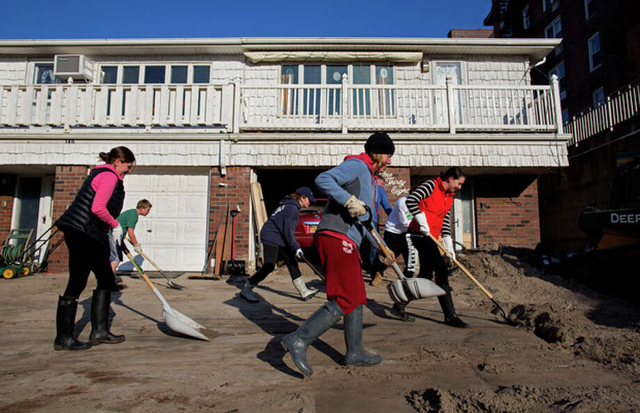 Neighbors volunteering to help another neighbor in need move deep sand from the house on Beach 121 Street in the Rockaway Park neighborhood of the borough of Queens, New York, Sunday, Nov. 11, 2012, in the wake of Superstorm Sandy. (AP Photo/Craig Ruttle) / FR61802 AP