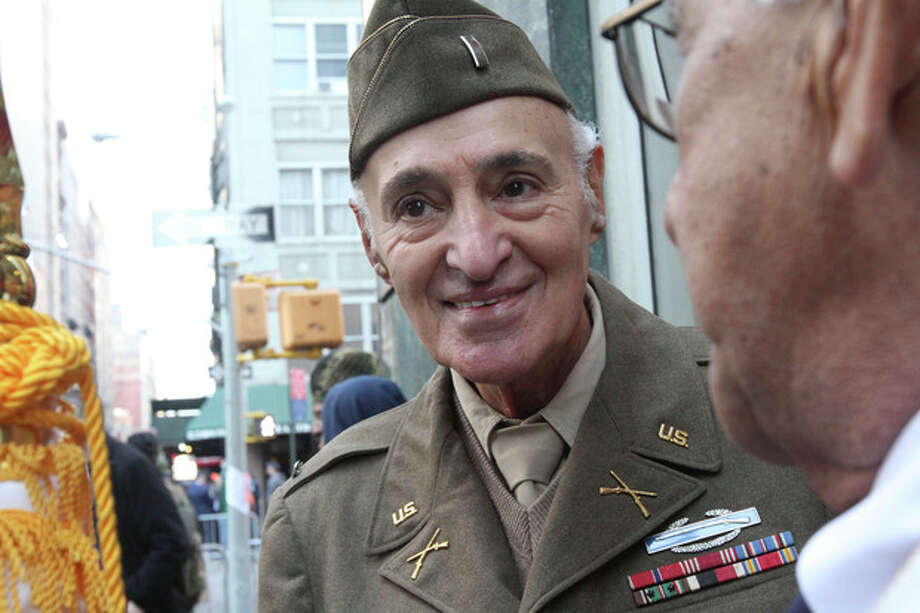 WWII veteran Eugene Cannava, 86, from New York, left, chats with Korean War veteran Samuel Benchimol, 81, from Glen Head, N.Y., as they wait to march up New York's Fifth Avenue in the Veterans Day Parade Sunday Nov. 11, 2012. (AP Photo/Tina Fineberg) / FR73987 AP