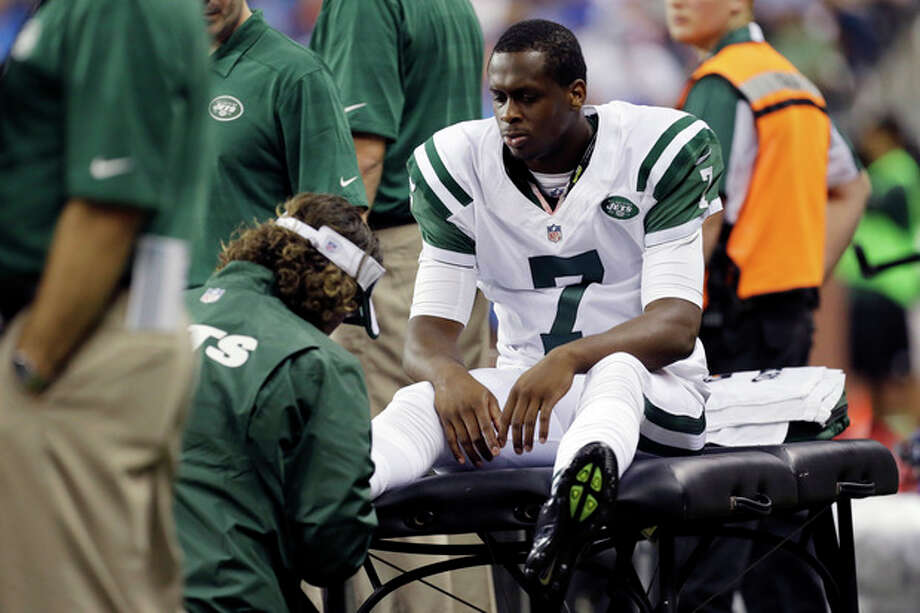 New York Jets quarterback Geno Smith (7) is examined during the third quarter of an NFL football game against the Detroit Lions at Ford Field in Detroit, Friday, Aug. 9, 2013. (AP Photo/Paul Sancya) / AP