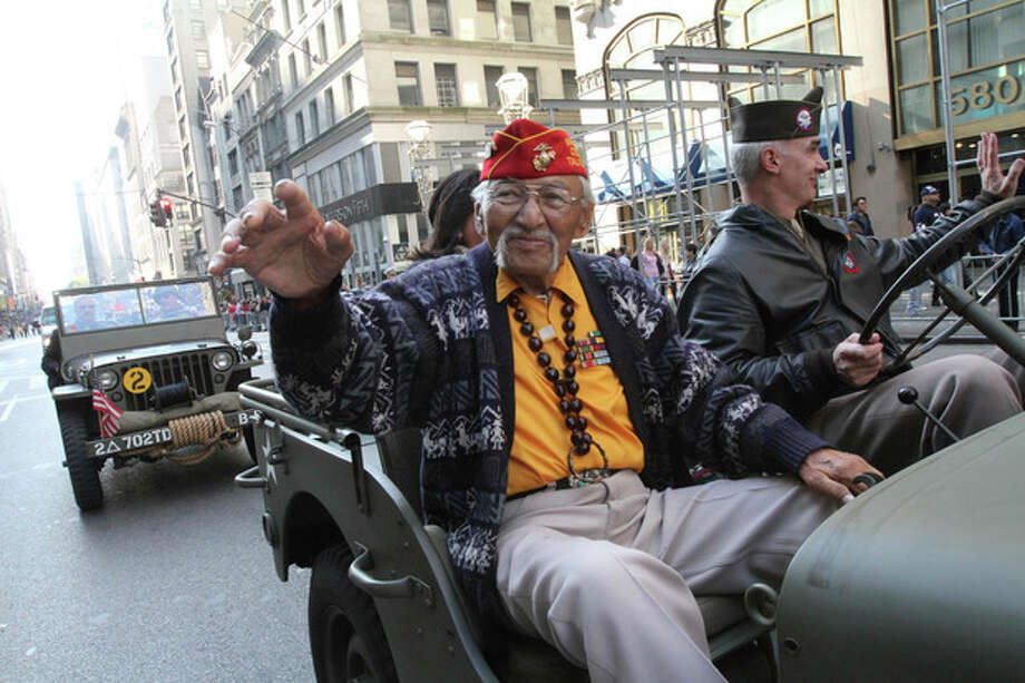 Navajo Code Talker WWII veteran Albert Smith, 89, left, waves as he rides up New York's Fifth Avenue in the Veterans Day Parade Sunday Nov. 11, 2012. (AP Photo/Tina Fineberg) / FR73987 AP