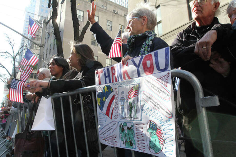 Holding a sign, Loretta Knapp, of the Bronx borough of New York, second from right, waves as she and others watch as the Veterans Day Parade makes it's way up New York's Fifth Avenue Sunday Nov. 11, 2012. (AP Photo/Tina Fineberg) / FR73987 AP