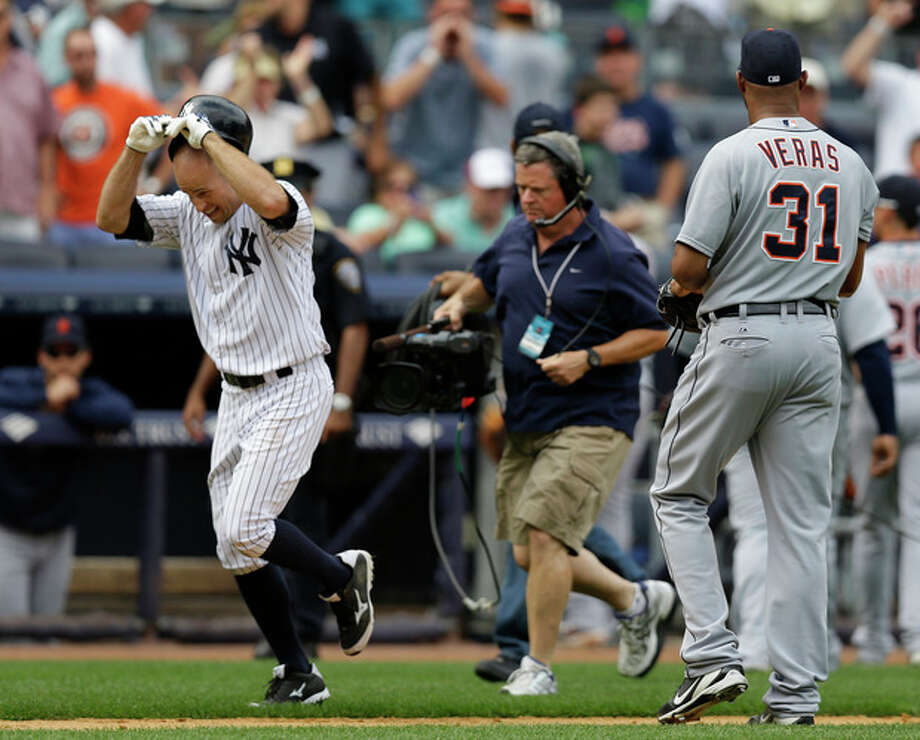 New York Yankees' Brett Gardner, left passes by Detroit Tigers relief pitcher Jose Veras (31) after hitting a ninth-inning walkoff, solo home run to lift the Yankees to a 5-4 victory in a baseball game on Sunday, Aug. 11, 2013, in New York. (AP Photo/Kathy Willens) / AP