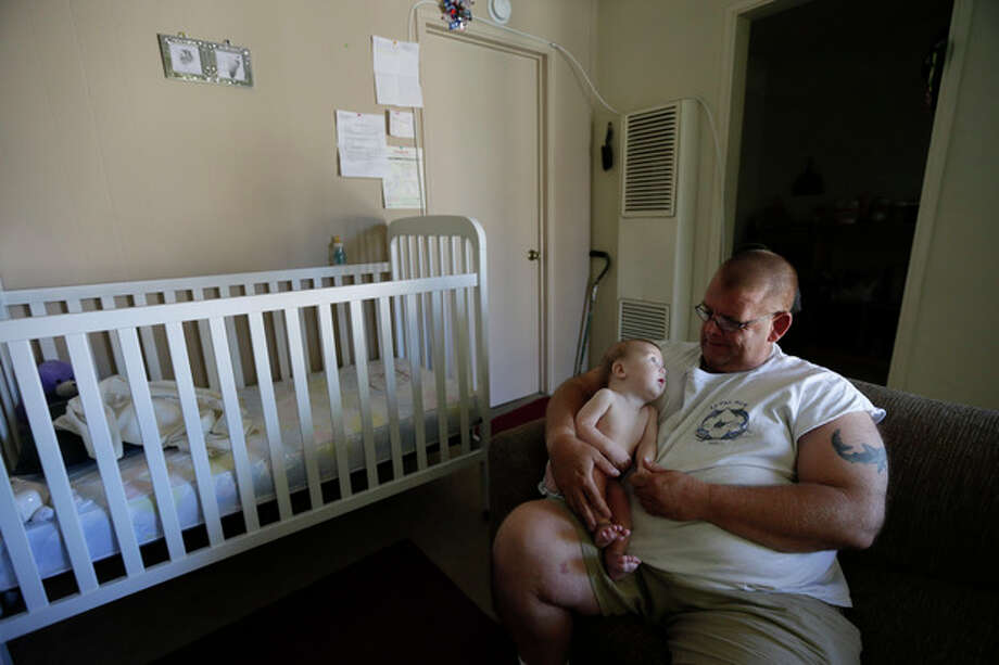In this Oct. 9, 2012 picture, veteran Arthur Lute holds his is 5-month-old son Evan in his one-bedroom apartment in Chula Vista, Calif. Lute's arduous journey from his days as a U.S. Marine to his nights sleeping on the streets illustrates the challenge the Obama administration faces to make good on its audacious promise: End homelessness among veterans by 2015. (AP Photo/Gregory Bull) / AP