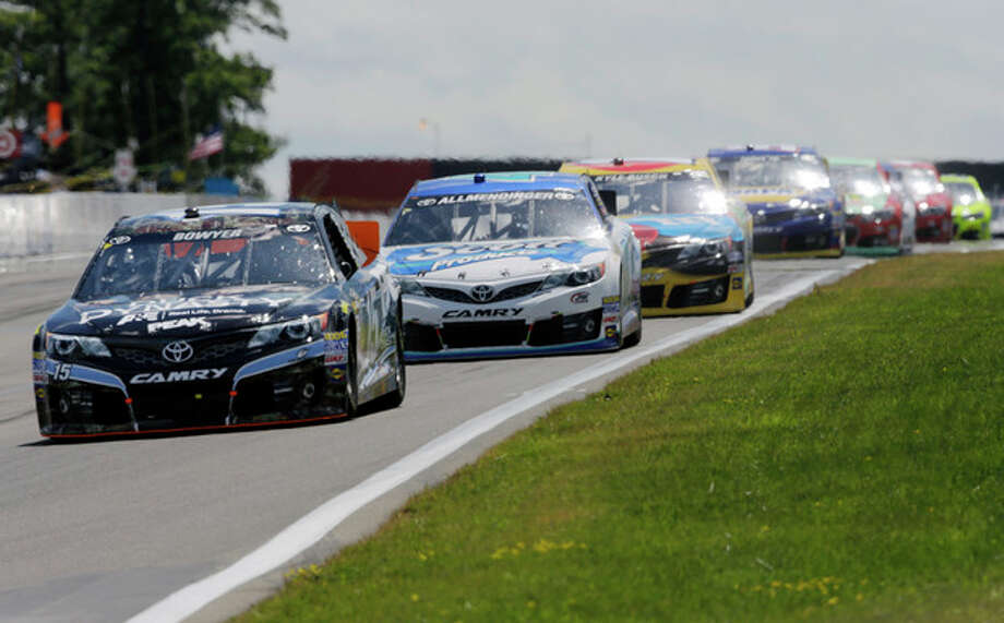 Clint Bowyer (15) leads a group of racers during a NASCAR Sprint Cup Series auto race at The Glen Sunday, Aug. 11, 2013, in Watkins Glen, N.Y. (AP Photo/Mel Evans) / AP