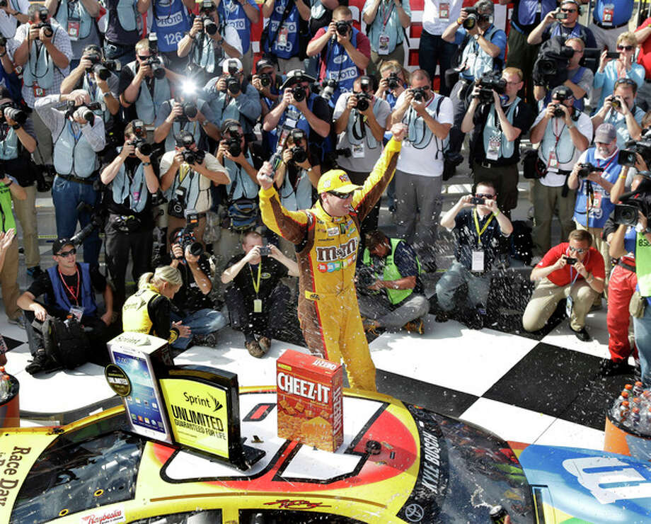 Driver Kyle Busch, center, celebrates in Victory Lane after winning a NASCAR Sprint Cup Series auto race, at The Glen Sunday, Aug. 11, 2013, in Watkins Glen, N.Y. (AP Photo/Mel Evans) / AP