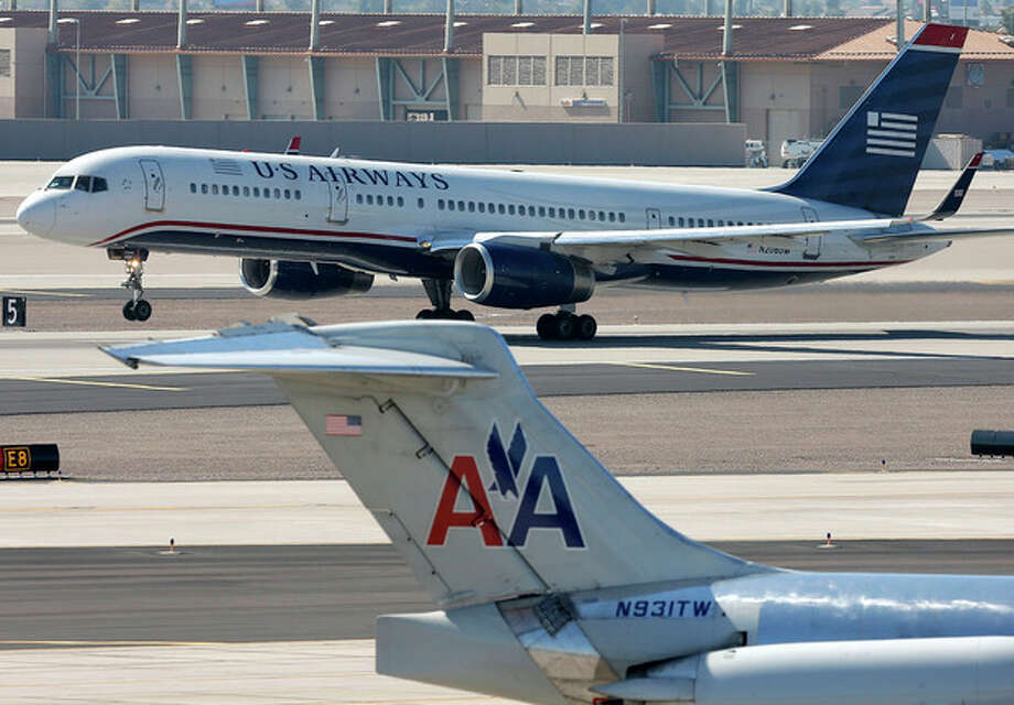 FILE - In this Thursday, Feb. 14, 2013, file photo, a U.S. Airways jet passes an American Airlines jet at Sky Harbor International Airport in Phoenix. The merger of the two airlines has given birth to a mega airline with more passengers than any other in the world. The Justice Department and a number of state attorneys general on Tuesday, Aug. 13, 2013, challenged a proposed $11 billion merger between US Airways Group Inc. and American Airlines' parent company, AMR Corp. (AP Photo/Matt York, file) / AP