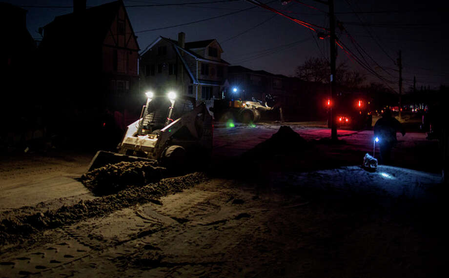 A front loader works to remove sand and debris as night falls on the Rockaway neighborhood in the Queens borough, of New York, Sunday, Nov. 11, 2012, in the wake of Superstorm Sandy. (AP Photo/Craig Ruttle) / FR61802 AP