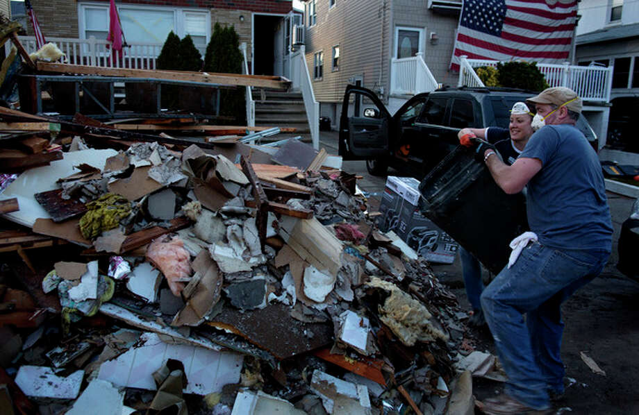 Volunteer Ashling Coleman and her husband Jerry Coleman of New York throw out the last load of debris for the day from the home of John and Ann Garvey, background left, which was damaged in the Rockaway Park neighborhood in the Queens borough of New York, Sunday, Nov. 11, 2012, from Superstorm Sandy. The Colemans, bringing other family members with them, came to the neighborhood today just to see if they could find anyone who needed help. They found the Garvey's home, offered their assistance, and were gladly welcomed in. (AP Photo/Craig Ruttle) / FR61802 AP