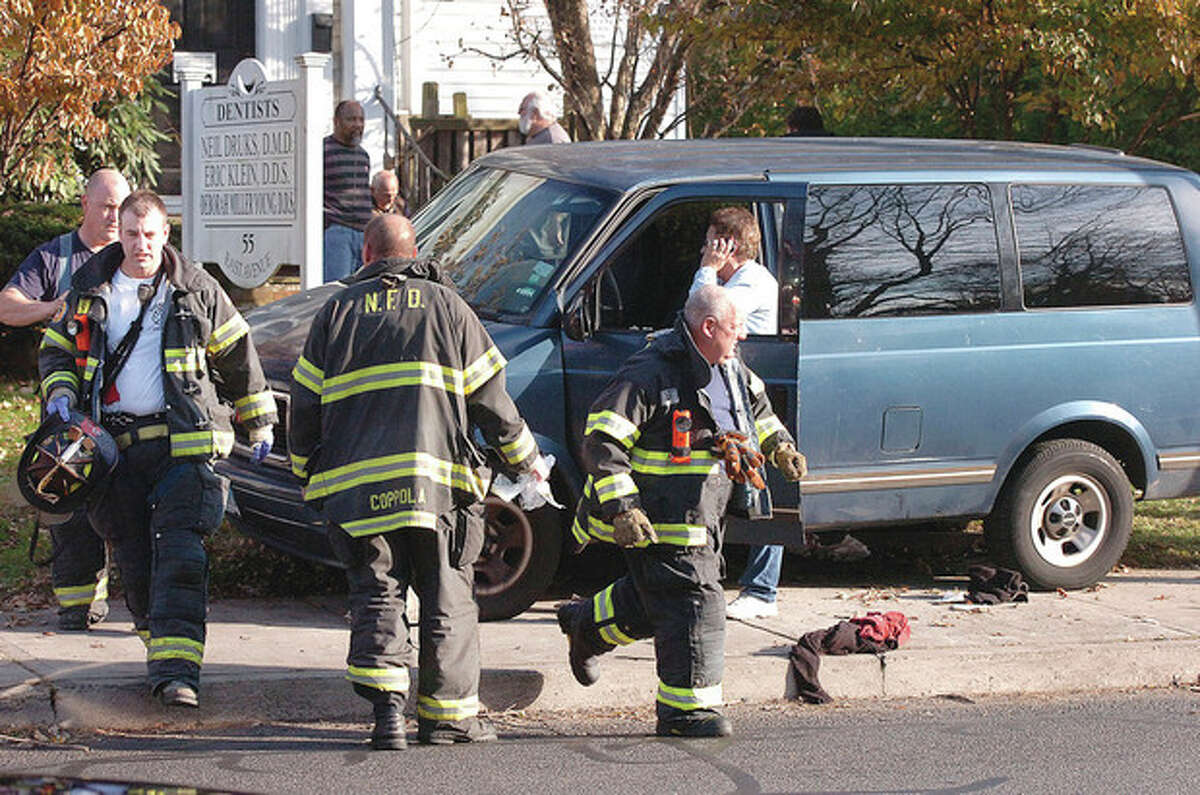 Hour Photo/Alex von Kleydorff Norwalk Firefighters respond to a pedestrian hit and trapped under a van that was being driven north on East Avenue at 2 p.m. on Monday.