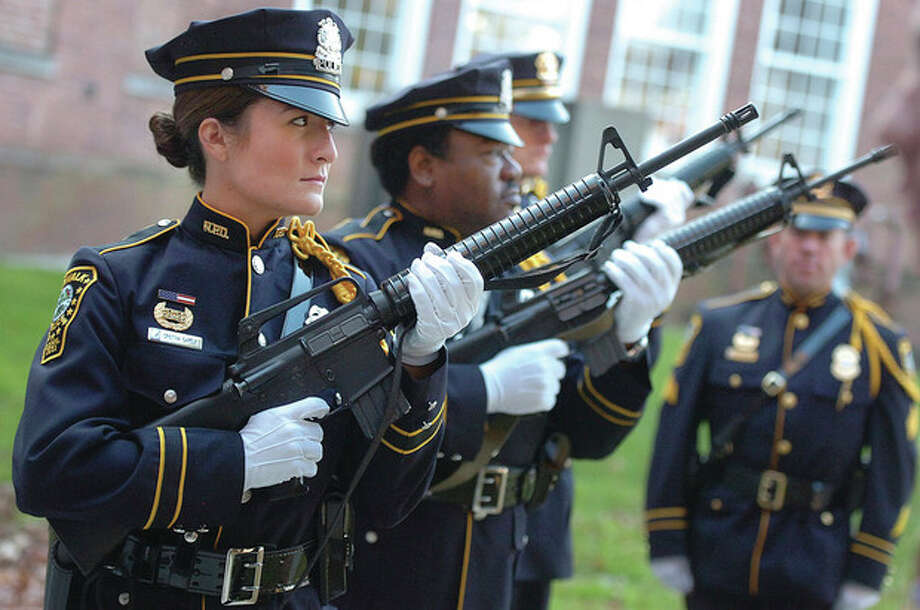 Hour photos/ Alex von KleydorffAt left, the Norwalk Police Honor Guard fires a Rifle Volley during Norwalks Veterans Day Ceremony. Above, from the left, Ladies Auxiliary 106 members Jeannette Burroghs and Evelyn Aman show thier support during the ceremony. Below, Vito Ottaviano salutes as the United States Marine Corps flag passes. At bottom,Keynote speaker Harry Rilling speaks Monday morning at the ceremony. / 2012 The Hour Newspapers