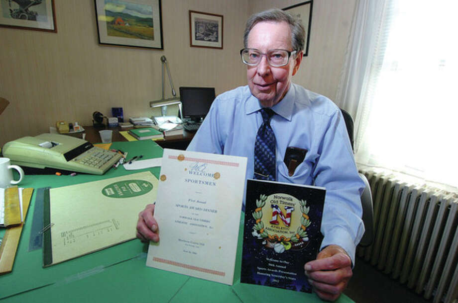 Hour photo/Alex von KleydorffJack Boone holds the programs for the first Norwalk Old Timers dinner, left, and and the 50th, which is coming up Wednesday night at Continental Manor. / 2012 The Hour Newspapers